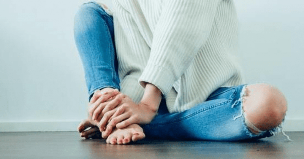 person wearing blue jeans holding her foot