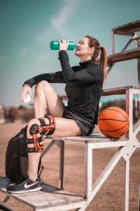 woman in black shirt and shorts with knee brace sitting next to orange basketball