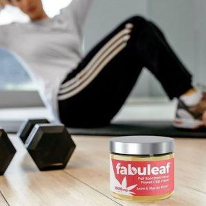 Person on yoga mat with dumbbells and fabuleaf full spectrum hemp flower cbd cream