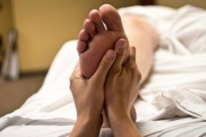 person massaging the bottom of a foot