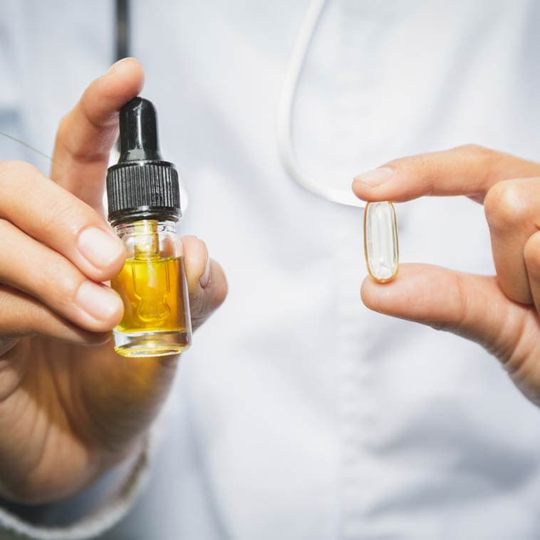 Hands holding CBD oil and CBD capsule | Comparing CBD Products Fabuleaf